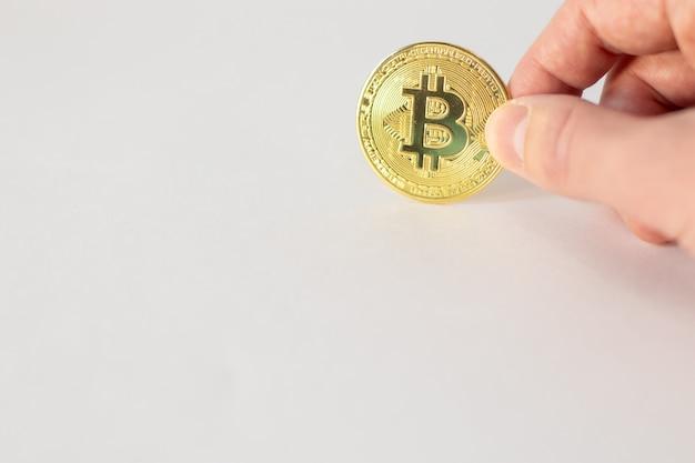 Hand met een gouden bitcoin geïsoleerd op een witte muur