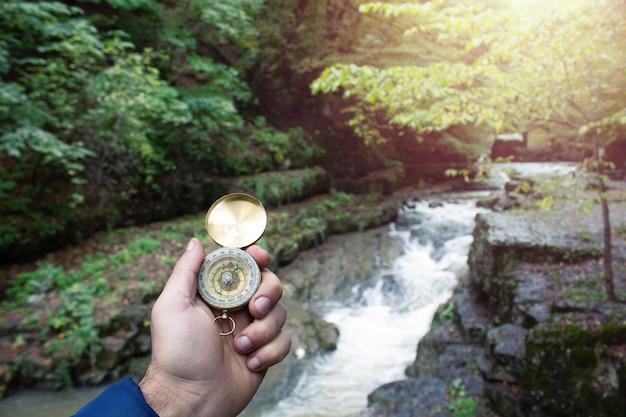 Hand met een gouden kompas op de achtergrond van de rivier