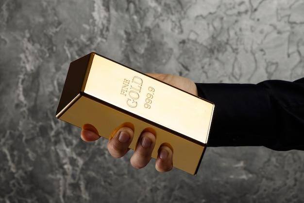 Hand met een goudstaaf