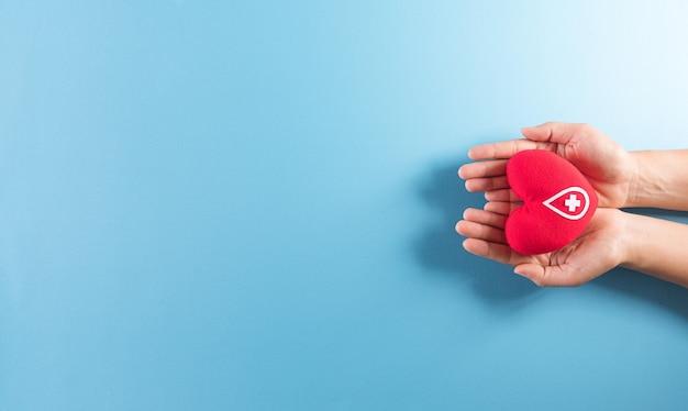 Hand met een handgemaakt rood hart met een teken of symbool van bloeddonatie