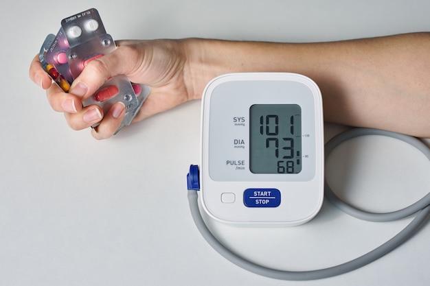 Hand met een handvol pillen en digitale bloeddrukmeter. gezondheidszorg en geneeskunde concept