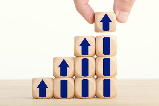 Hand met een houten blok met stijgende pijlpictogram