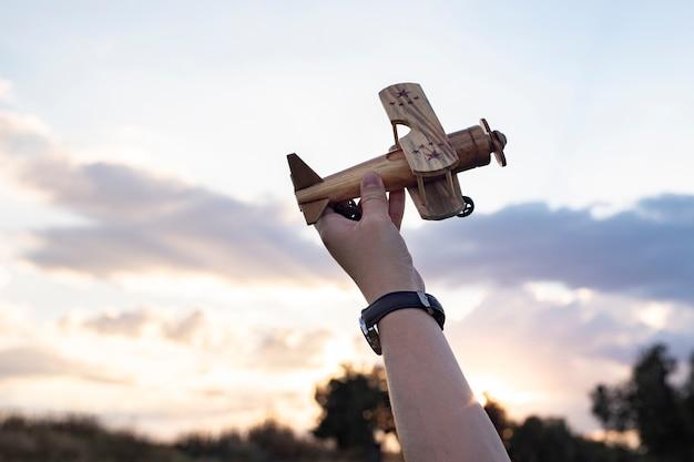 Hand met een houten vliegtuig vakantie concept