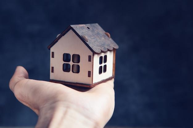 Hand met een huis op een zwarte achtergrond