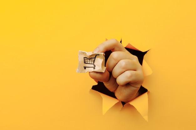 Hand met een kapotte bezorgdoos door een geel papiergat.