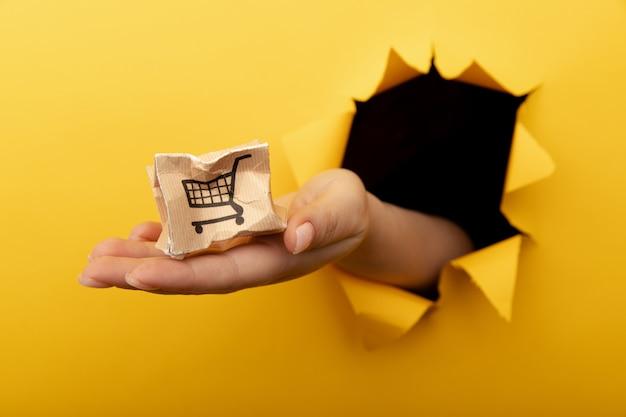 Hand met een kleine kapotte afleveringsdoos door een geel papieren gat in de bezorgdienst