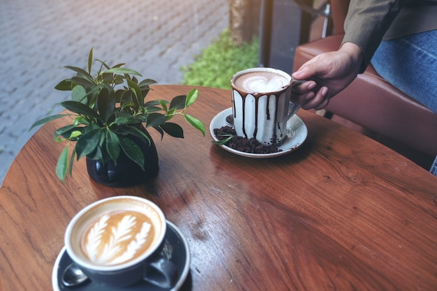 Hand met een kop warme chocolademelk met een ander kopje koffie op houten tafel in café