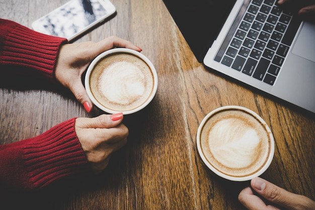 ็ hand met een kop warme latte koffie en mobiele telefoon met vriend werken
