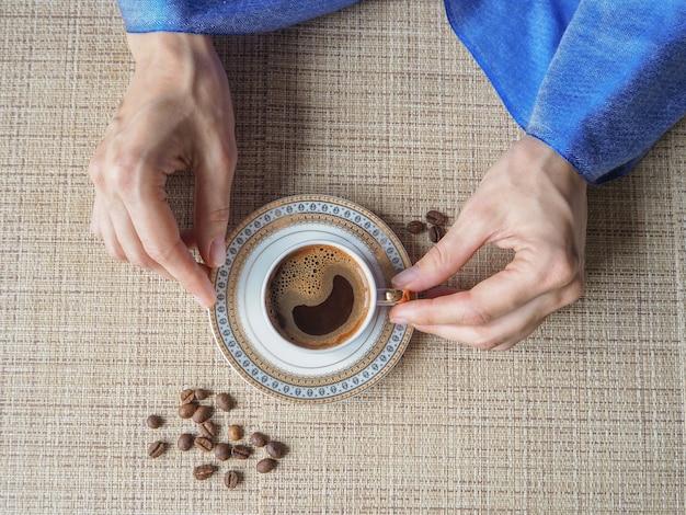 Hand met een kopje koffie. de hand houdt een elegante kop koffie.