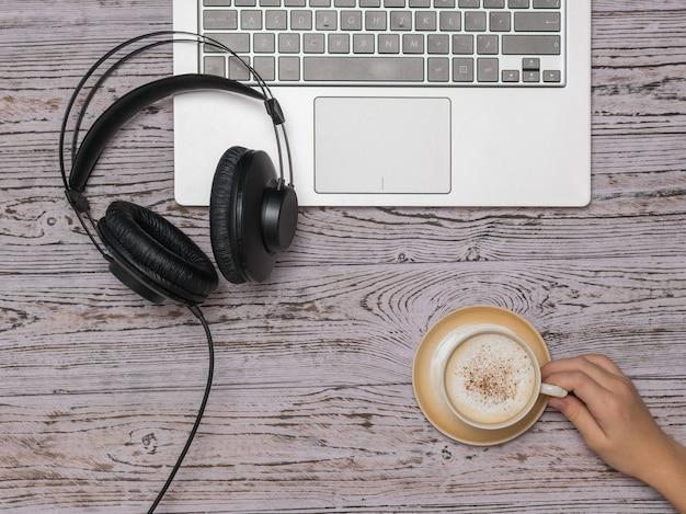 Hand met een kopje koffie, een laptop en koptelefoon op een houten tafel