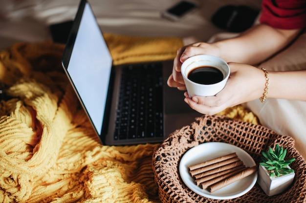 Hand met een kopje koffie en ontbijtschotel met laptop op het bed Premium Foto