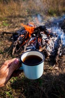 Hand met een kopje koffie naast een kampvuur