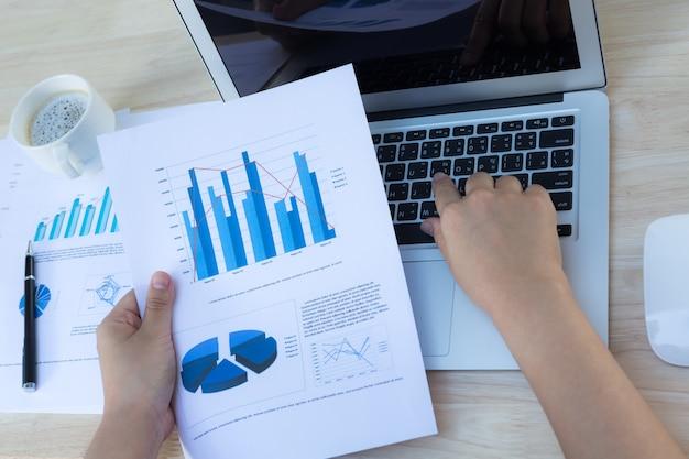 Hand met een laptop en een aantal documenten met graphics