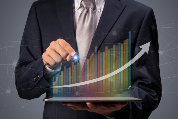 Hand met een laptop met slimme services voor succesvolle investeringen met groei-inkomstengrafiek