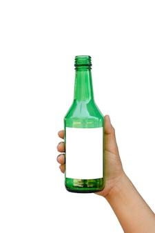 Hand met een lege groene glazen fles met een tekstruimte geïsoleerd op een witte achtergrond met het uitknippad.