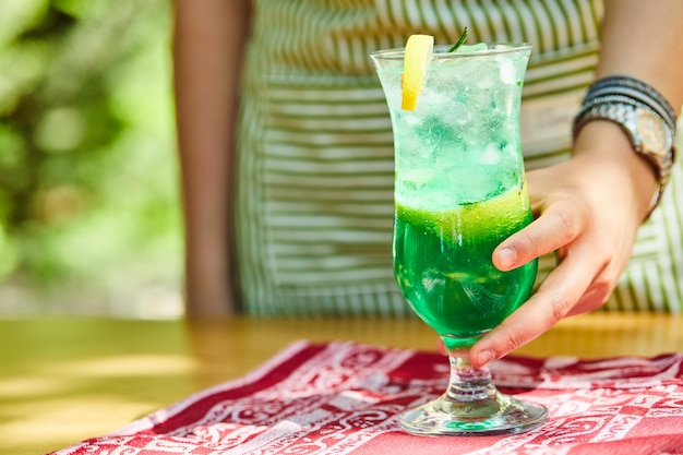 Hand met een limonade op houten tafel.
