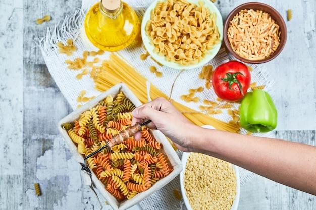 Hand met een mandje rauwe fusilli pasta met diverse pasta's en groente op de marmeren tafel.