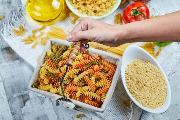Hand met een mandje van rauwe fusilli pasta met diverse pasta en groente op de marmeren tafel.