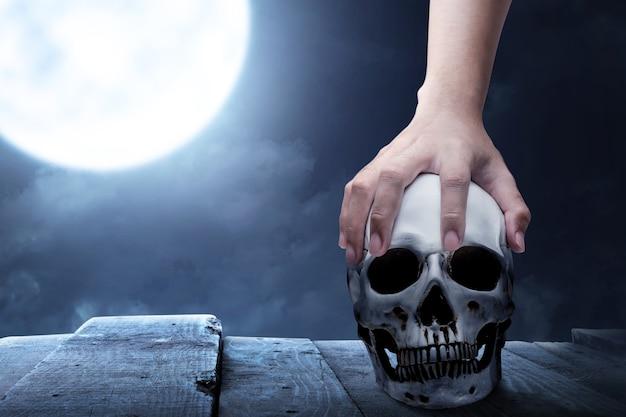 Hand met een menselijke schedel op een houten tafel met de achtergrond van de nachtscène