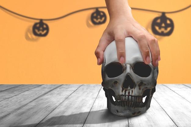 Hand met een menselijke schedel op een houten tafel met gekleurde achtergrond