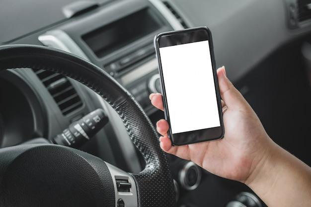 Hand met een mobiel in een auto
