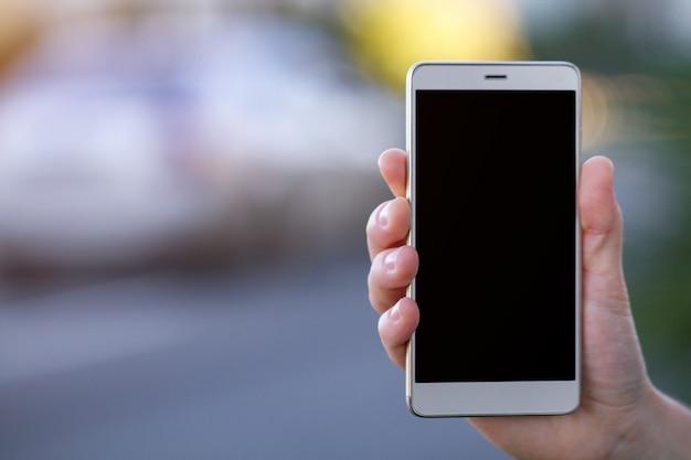Hand met een mobiele telefoon met zwart scherm in de straat