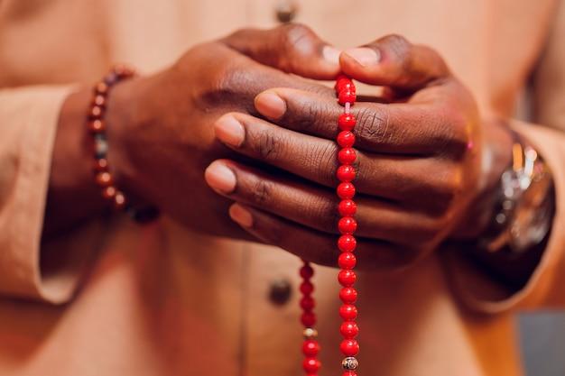 Hand met een moslim kralen rozenkrans of tasbih op een bidmat, bid tot god. ramadhan kareem.