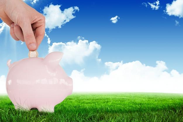 Hand met een munt op een roze spaarvarken