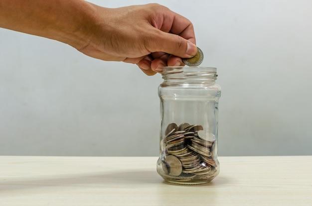 Hand met een muntstuk in een glazen pot. bedrijfsconcept om geld te besparen. financiële en investeringsplanning voor de toekomst.