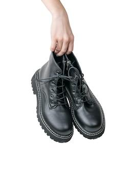 Hand met een paar zwarte geïsoleerde leerschoenen. casual schoenen.