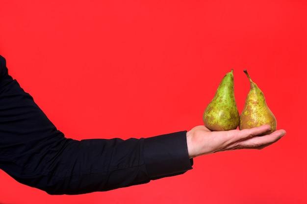 Hand met een peer twee op rode achtergrond