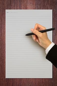 Hand met een pen op een gestreepte papier