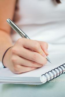 Hand met een pen over notebook