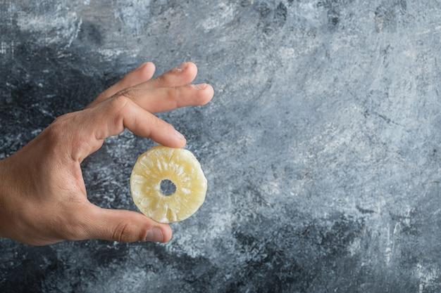 Hand met een plakje gedroogde ananas op een grijze achtergrond.