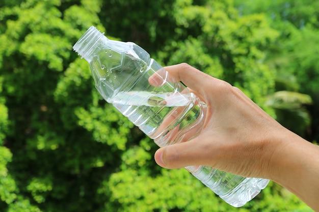 Hand met een plastic fles drinkwater tegen groen gebladerte