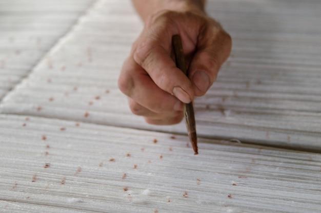 Hand met een potlood maakt markeringen op het tapijt weven en vervaardigen van handgemaakte tapijten close-up