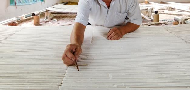 Hand met een potlood maakt sporen op het tapijt weven en vervaardigen van handgemaakte tapijten