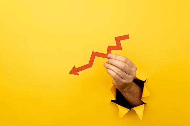 Hand met een rode pijl naar beneden door een geel papiergat.