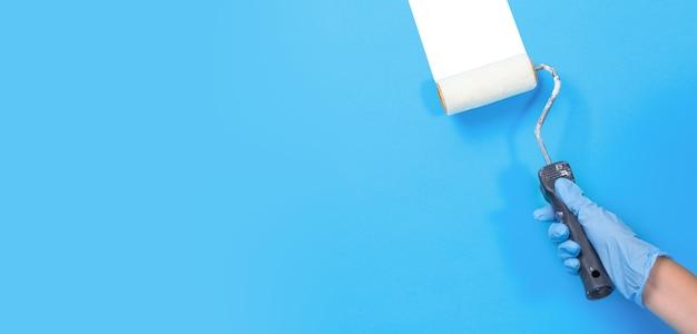 Hand met een roller voor het schilderen van muren, blauwe muur, plaats voor tekst. huisreparatie handen van werknemer schilderij muur in kamer.