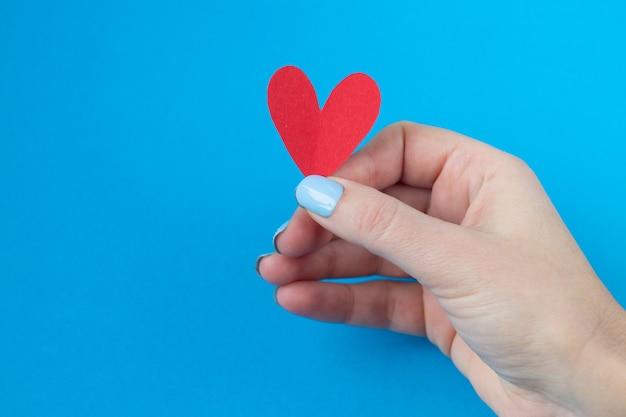 Hand met een rood hart op een blauwe achtergrond. achtergrond voor valentijnsdag