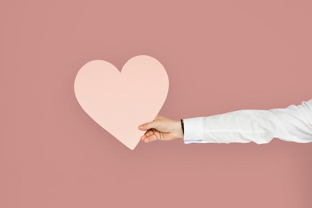 Hand met een roze hartuitsparing, gezond hart of liefdesconcept