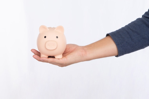 Hand met een roze spaarvarken geïsoleerd op een witte achtergrond