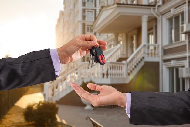 Hand met een sleutel over nieuwe huisachtergrond.