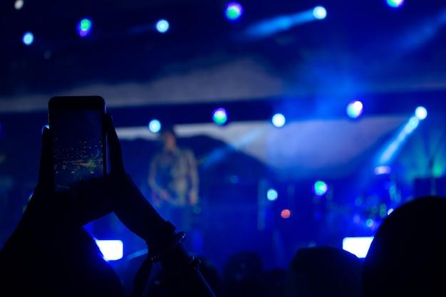 Hand met een smartphone neemt live muziekfestival op