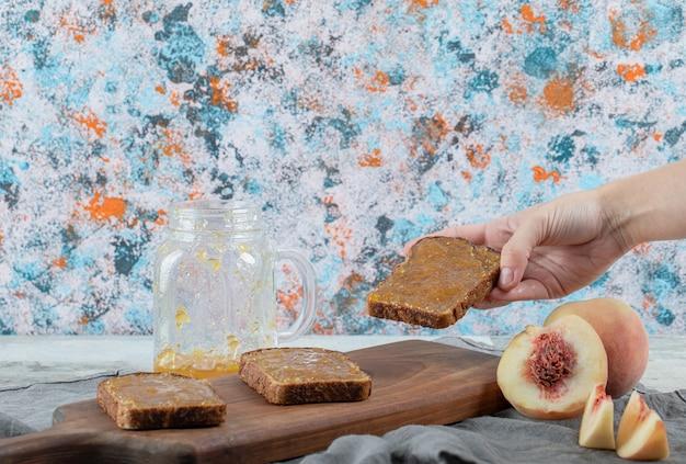 Hand met een sneetje brood met perzikjam.