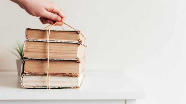 Hand met een stapel oude boeken in de bibliotheek, concept van leren, studeren en onderwijs, concept van wetenschap, wijsheid en kennis.