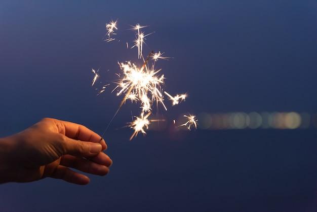 Hand met een sterretje op strand tijdens zonsondergang. viering concept.