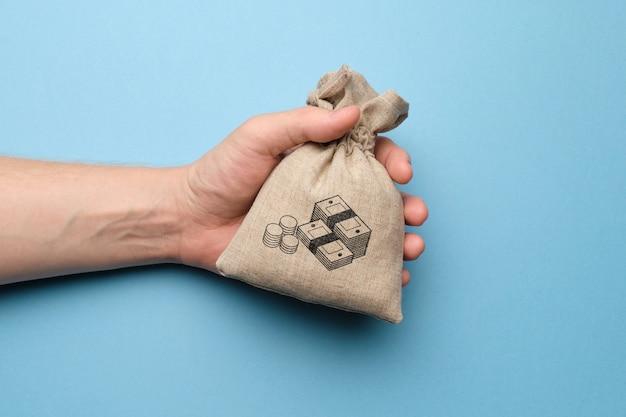 Hand met een tas met een afbeelding van geld.