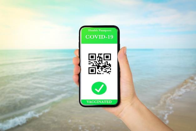 Hand met een telefoon met green pass-verificatie voor covid19 op zeeachtergrond