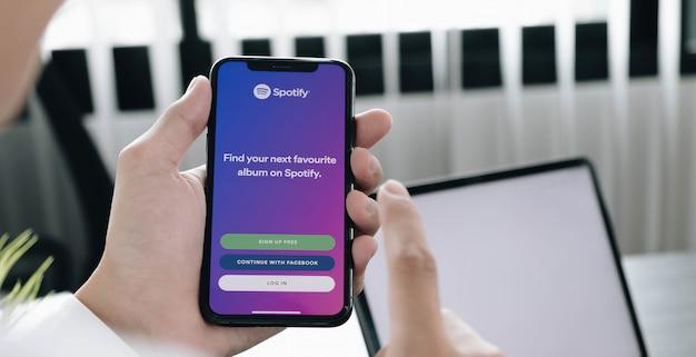 Hand met een telefoon met spotify-app inloggen op het scherm